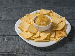 Mexican tortilla chips with cheese and mustard in a clay bowl on a black wooden table. A dish of Mexican cuisine.