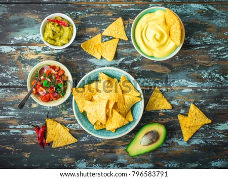 Mexican tortilla chips with guacamole, cheese, salsa dips. Nachos and assorted dips. Mexican party food, appetizers. Top view. Tortilla chips, sauces, hot pepper, avocado, rustic wooden background #796583791