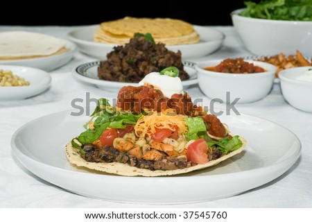 Mexican tostada or taco with black beans, chicken, lettuce, tomatoes, cheddar cheese, salsa, sour cream, and jalapeno peppers