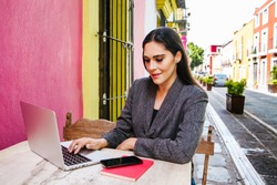 Mexican woman working with her computer on a coffee shop terrace in the streets of a colonial city in Latin America