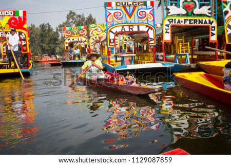 Mexican workers painting colorful trajineras boats in xochimilco, Mexico City, Mexico. 2016-12-19. #1129087859
