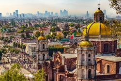 Mexico. Basilica of Our Lady of Guadalupe. Cupolas of the old basilica and cityscape of Mexico City on the far
