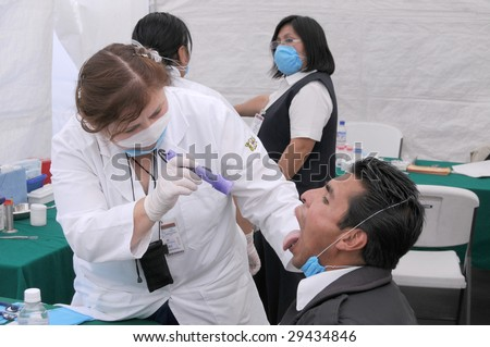 MEXICO CITY - APRIL 29: A doctor examines a flu patient for signs of Swine Flu at a clinic on April 29, 2009 in Mexico City. Reports of approximately 148 cases exist in about nine countries to-date.