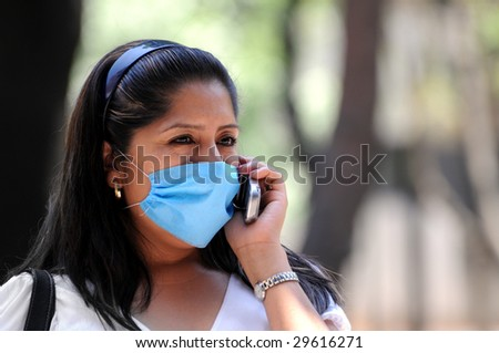 MEXICO CITY - APRIL 30:A woman talks on her cellphone while protecting herself against influenza with a face mask on April 30, 2009 in Mexico City.