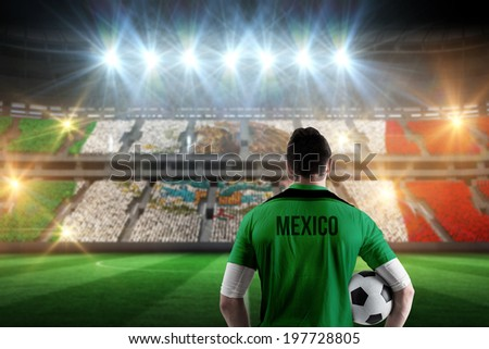 Mexico football player holding ball against stadium full of mexico football fans