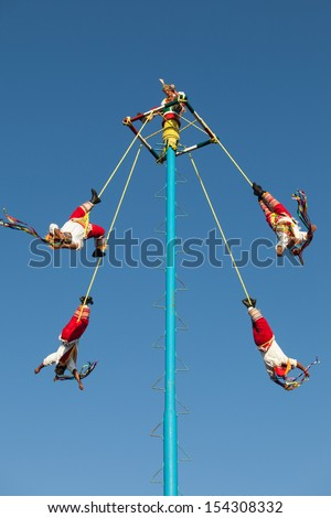 "MEXICO, RIVIERA MAYA, PLAYA DEL CARMEN - MARCH 4: Acrobat performers (Voladores) at ""Flying Men Dance"" ceremony on March 4, 2013. The ritual in ancient times to please the God of rain."