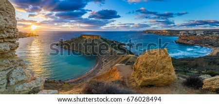 Mgarr, Malta - Panorama of Gnejna bay and Golden Bay, the two most beautiful beaches in Malta at sunset with beautiful colorful sky and golden rocks taken from Ta Lippija