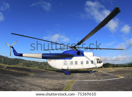 MI-8 Helicopter on takeoff in the mountains against the blue sky