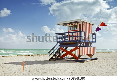 Miami Beach, Florida colorful lifeguard building painted with stripes and stars resembling the USA flag. Beautiful sunny day with blue sky and ocean in the background