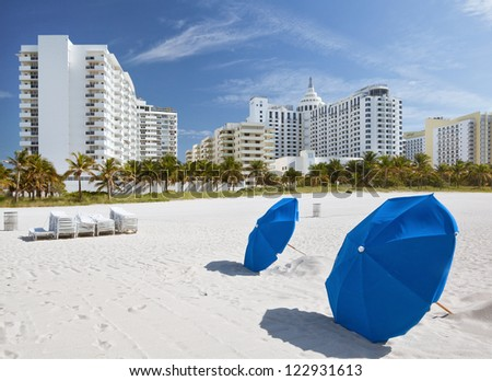 Miami Beach, Florida, sunny summer day, blue umbrellas and lounge chairs with modern architecture buildings. Famous travel location.