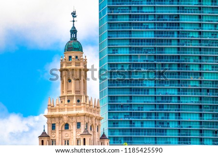 Miami city architectural contrast: the Freedom Tower against a modern high rise building. The old building is a tourist attraction #1185425590