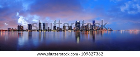 Miami city skyline panorama at dusk with urban skyscrapers over sea with reflection