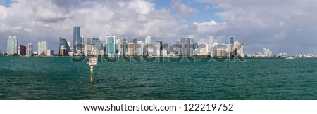 Miami cityscape skyline from Rickenbacker causeway on cloudy morning with Manatee zone slow speed sign