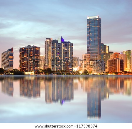 Miami Florida, cityscape of illuminated downtown buildings at sunset with reflections in the water of Biscayne Bay. Panoramic skyline of the World famous travel location