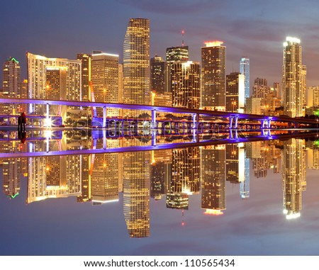 Miami Florida illuminated downtown buildings at night with reflections in the water of Biscayne Bay. Panoramic skyline of the World famous travel location - stock photo