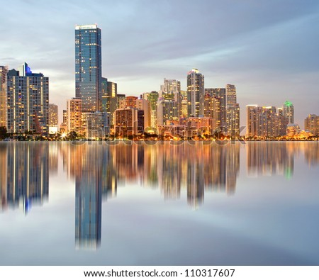 Miami Florida illuminated downtown buildings at sunset with reflections in the water of Biscayne Bay. Panoramic skyline of the World famous travel location