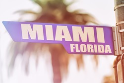 Miami Florida Street Sign. A street sign marking Miami, Florida. Backed by a palm tree with a sunset flare.