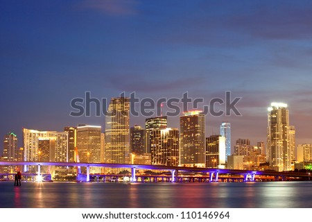 Miami Florida sunset over downtown business and luxury residential buildings, hotels and illuminated bridge over Biscayne Bay.  Cityscape of World famous travel destination.