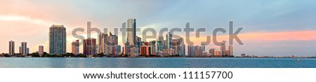 Miami Florida sunset over downtown business and luxury residential buildings, hotels and illuminated bridge over Biscayne Bay. Panoramic colorful Cityscape of World famous travel destination.