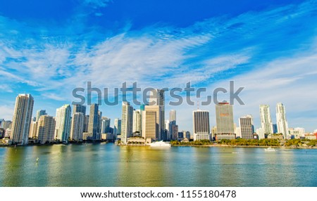 miami life and real estate property.Aerial view of Miami skyscrapers with blue cloudy sky,white boat sailing next to Miami downtown