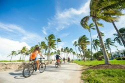 MIAMI - SEPTEMBER, 2018: Visitors and locals ride bicycles along the beachfront promenade in Lummus Park adjacent to historic Ocean Drive.