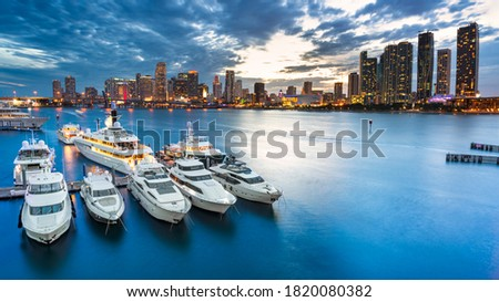 Miami skyline at dusk on cloudy evening with dramatic sky showing brickell and downtown and the marina in the foreground with the large impressive yachts and boats