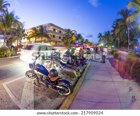 MIAMI, USA - AUG 23, 2014: Palm trees and art deco hotels at Ocean Drive by night. The road is the main thoroughfare through South Beach in Miami, USA.