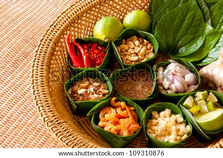Miang Kham is a tasty snack often sold as Thailand street food. It involves wrapping little tidbits of several items in a leaf, along with a sweet-and-salty sauce.