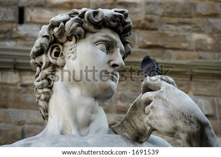 Michelangelo's replica David statue conversing with a pigeon. - stock photo