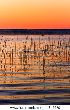 Michigan's Platte Lake photographed just before sunrise with a row boat floating in the distance