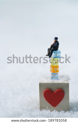 Micro doll sitting on heart box and plastic blocks spelling \
