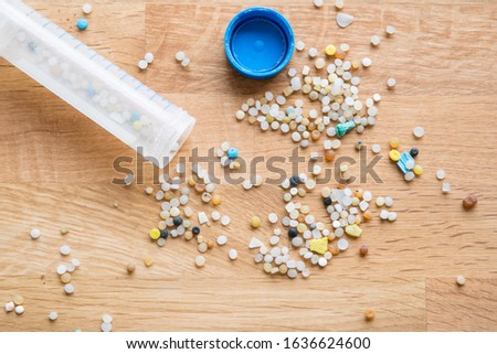 Micro plastic granulate and pieces collected in a lab tube, found on a beach in Norway, spread out on a wooden table. Containing both degrading plastic parts as granulate used for plastic production.