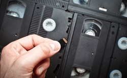 Micro sd memory card in hand on a background of video cassettes. Comparison of modern and retro technologies.