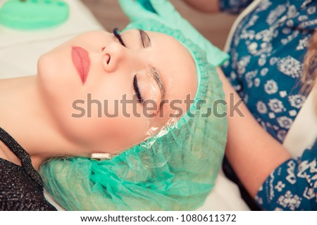 Microblading eyebrows work flow in a beauty salon. Technician is preparing for tattoo application. Woman having her eye brows tinted. Semi-permanent makeup for eyebrows. Focus on eyebrow closed eyes.