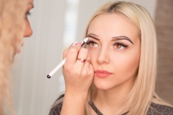 Microblading, micropigmentation eyebrows work flow in a beauty salon. Woman having her eye brows drawn and tinted with black pencil, preparing for semi-permanent makeup for eyebrows. Focus on eyebrow