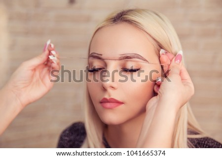 Microblading, micropigmentation eyebrows work flow in a beauty salon. Woman having her eye brows drawn and tinted. Semi-permanent makeup for eyebrows. Focus on eyebrow