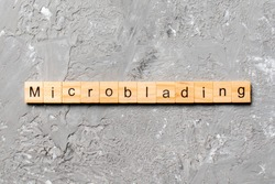 Microblading word written on wood block. Microblading text on cement table for your desing, concept.