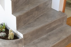 Microcement grey colour on staircase with matt finish, in combination with white walls and natural wooden floor