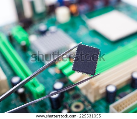 microchip in the tweezers on the background of the motherboard #225531055