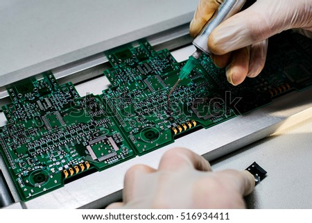 Microchip production factory. Technological process. Assembling the board. Chip. Professional. Technician. Computer expert. Manufacturing. Engineering. The assembly of computer units.