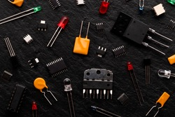 Microcontrollers, transistors, green, red, blue and transparent LEDs, microcircuits, capacitors, thyristors on a black stone background. Radio components