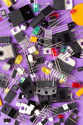 Microcontrollers, transistors, green, red, blue and transparent LEDs, microcircuits, capacitors, thyristors on a purple background. Radio components