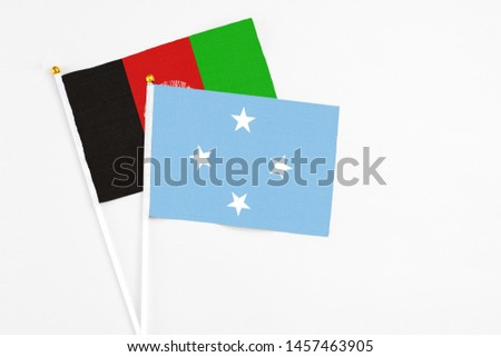 Micronesia and Afghanistan stick flags on white background. High quality fabric, miniature national flag. Peaceful global concept.White floor for copy space.