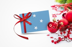 Micronesia flag on new year invitation card with red christmas ornaments concept. National happy new year composition.