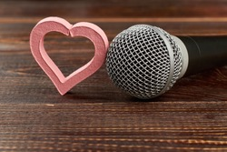 Microphone and heart on wooden background. Gray microphone and pink heart shaped decoration on brown wooden table. This is love song. For music lovers.