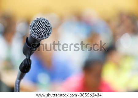 Microphone close up shot in seminar or meeting room with people in blur focus for copy space
