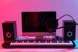 Microphone, computer and musical equipment guitars and piano background. Home recording studio concept.