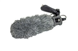Microphone for documentary filming and has wind-noise suppression material