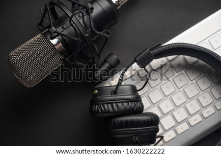 Microphone for podcasts and studio headphones on a PC keyboard on a black background, horizontal frame