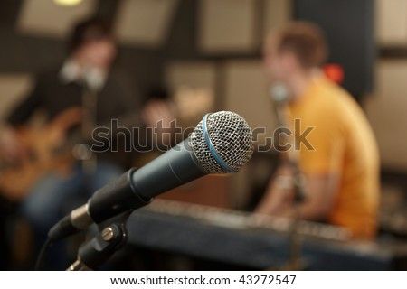 microphone. guitar player and keyboarder in out of focus